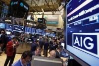 The American International Group, Inc. (AIG) stock ticker is seen on a monitor as traders work on the floor of the New York Stock Exchange